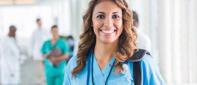 A smiling medical assistant in a clinical setting.