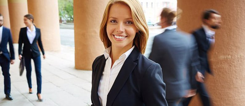 A close up of a smiling legal assistant outside in a law office courtyard.