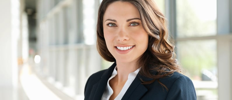 A close-up of a smiling business woman in the bright hallway of an office building.
